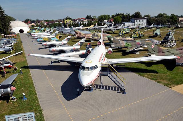 Zdjęcie przedstawia rożne samoloty i helikoptery stojące obok siebie w przestrzeni muzeum.