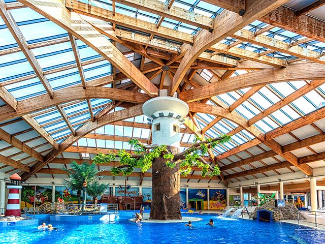 Zdjęcie przedstawia ogromną halę z basenami, z centralnie usytuowaną kolumną stylizowaną na drzewo, na której oparte jest sklepienie z drewnianych beli.