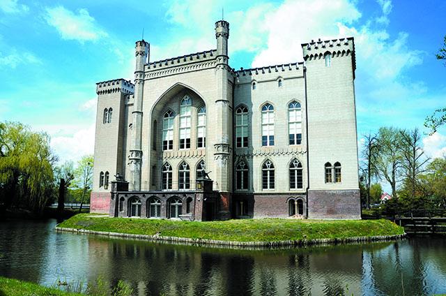 Zdjęcie przedstawia fasadę zamku w Kórniku otoczonego wypełnioną wodą fosą.