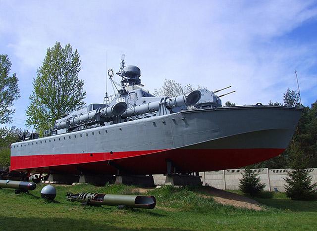 Zdjęcie przedstawia model okrętu wojennego w pomniejszeniu, stojącego na podstawach
