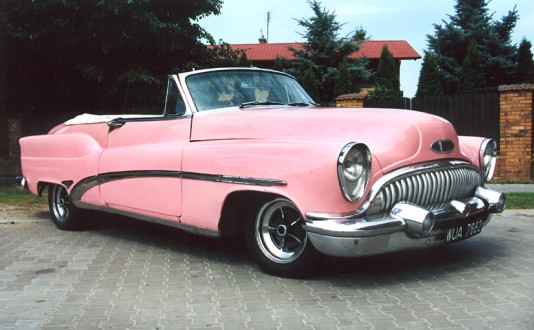 Zdjęcie przedstawia stary, różowy samochód bez dachu marki Cadillac.