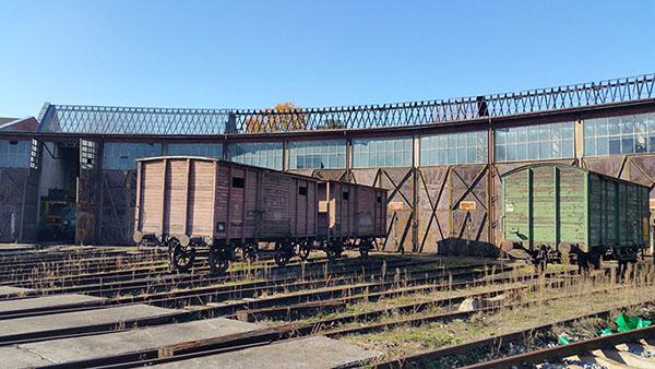 Zdjęcie przedstawia hale wachlarzową i stojące przed nią drewniane wagony.