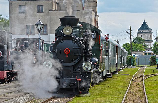 Zdjęcie przedstawia lokomotywę parową kolei wąskotorowej ciągnącą wagony pasażerskie.