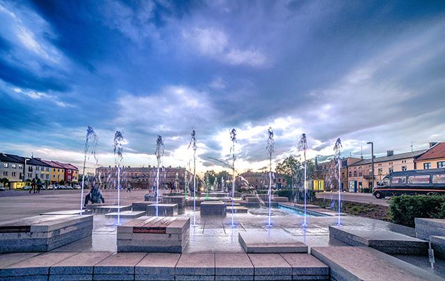 Zdjęcie przedstawia fontanny na placu otoczonym kamienicami.
