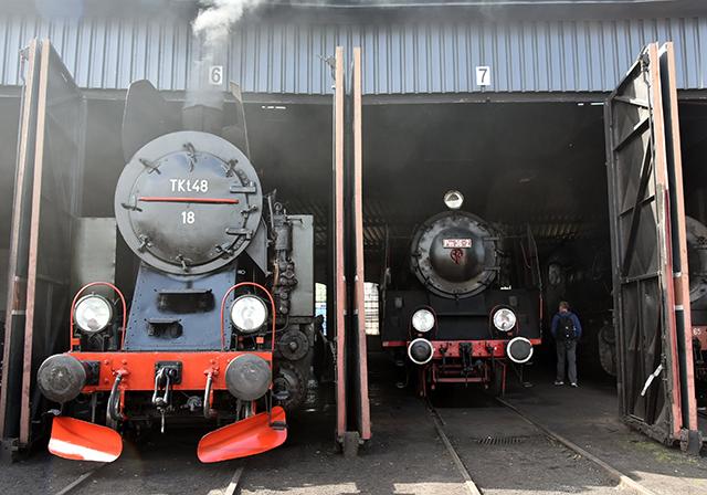 Zdjęcie przedstawia lokomotywy parowe wyjeżdżające z hali wachlarzowej.