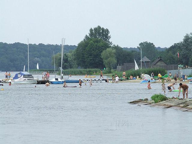 Zdjęcie przedstawia brzeg zbiornika wodnego, pomosty i łódki, a także ludzi plażujacych i kąpiących się.